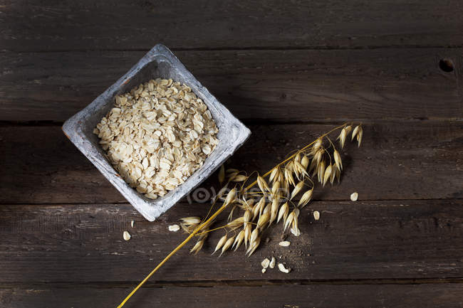 Bowl with oat flakes and ripe spike of oat on wood — Stock Photo
