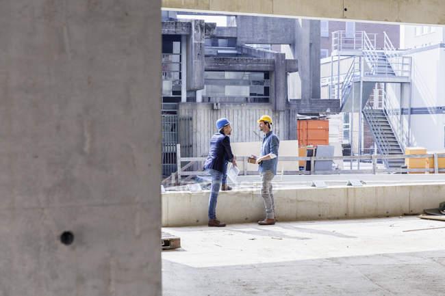 Двоє чоловіків з каски говорити на будмайданчик — стокове фото