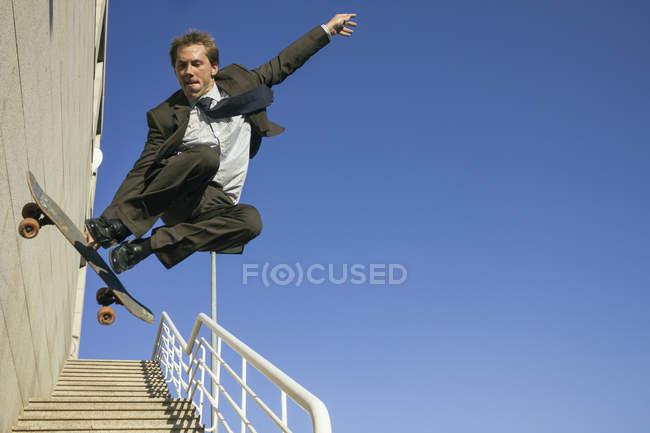 Homme d'affaires, faire des truc en l'air avec la planche à roulettes — Photo de stock