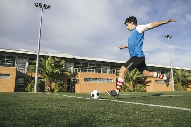 Fußballer kickt einen Ball — Stockfoto
