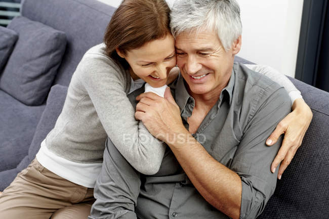 Happy couple sitting together on couch — Stock Photo