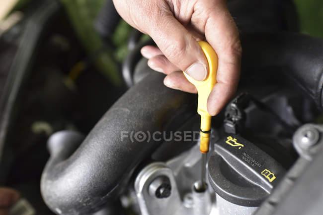 Крупным планом автомобиль механик проверки уровня масла в ремонт гаража — стоковое фото