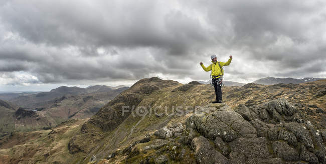 England, Cumbria, Lake District, Langdale, Harrison Stickle, climber holding hands up on the rock — Stock Photo