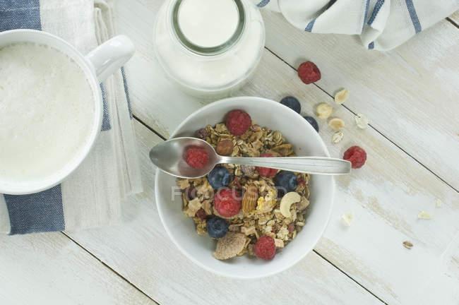 Сніданок з мюслі та фруктами, капуччіно і пляшка молока — стокове фото