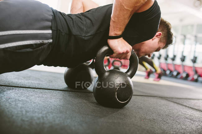 CrossFit athlete doing push-ups on kettlebells — Stock Photo