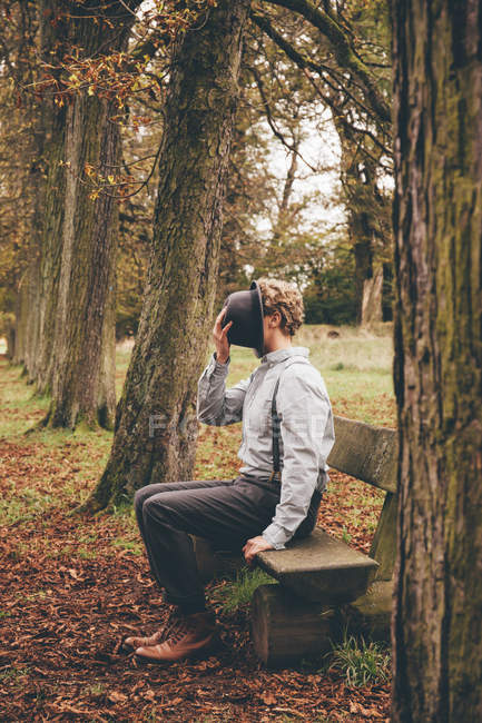Young man sitting on a bench in autumnal park covering his face with a hat — Stock Photo