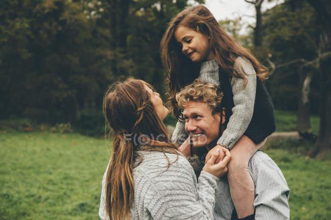 Feliz pareja joven con una niña sobre los hombros de su padre en el parque otoñal - foto de stock