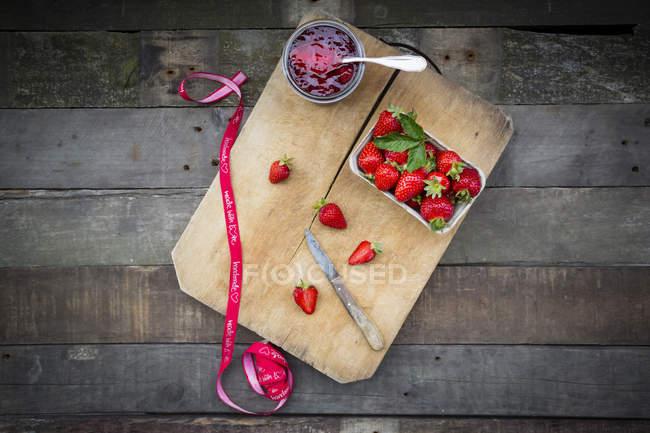 Copo de geléia de morango caseiro e caixa de morangos frescos em tábua de madeira — Fotografia de Stock