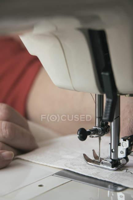 Руки женщины с помощью швейной машинки — стоковое фото