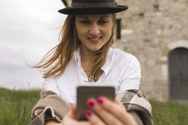 Young woman on a meadow listening music with earphones and smartphone — Stock Photo