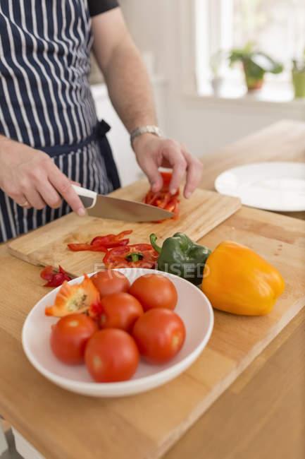 Mann schneidet Gemüse auf Holzschneidebrett — Stockfoto