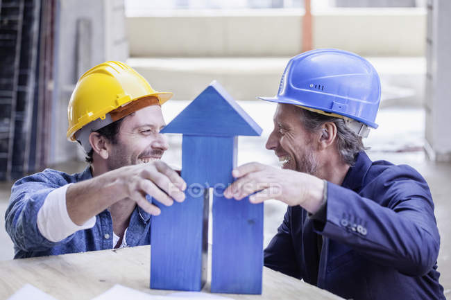 Two happy men with hard hats and model house — Stock Photo