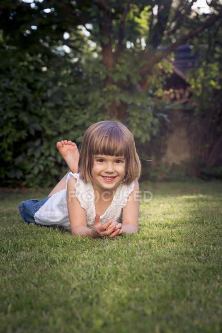 Улыбающаяся маленькая девочка лежит на лугу в саду — стоковое фото