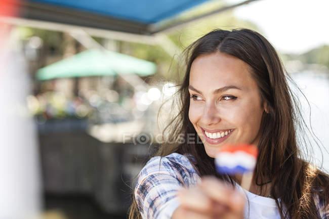 Olanda, Amsterdam, giovane donna sorridente che tiene piccola bandiera olandese — Foto stock