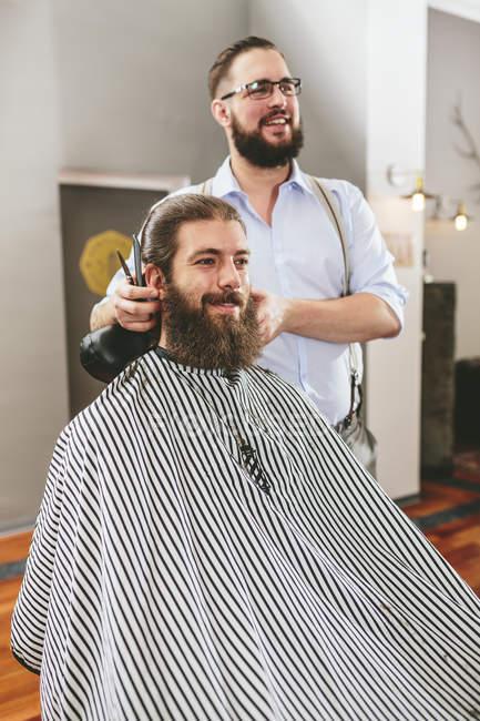 Цирюльник бороды резки заказчика и глядя в зеркало — стоковое фото