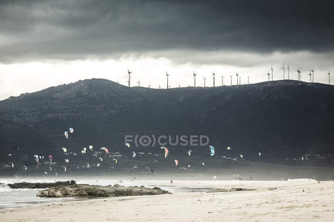 Spain, Andalusia, Tarifa, Kiter in front of mountain with wind wheels — Stock Photo