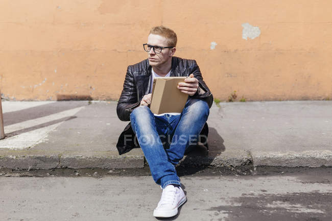 Young man with digital tablet sitting at curb — Stock Photo