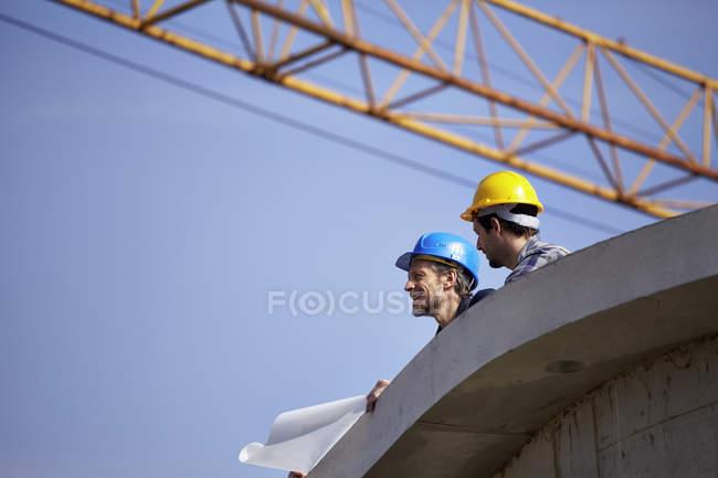 Dois homens no local de construção com planta da construção — Fotografia de Stock