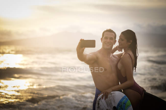 Young couple taking a selfie on beach at twilight — Stock Photo