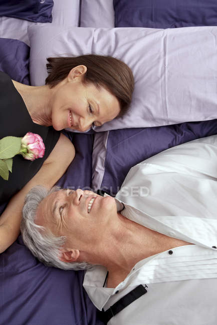Mature couple in love lying on bed looking at each other — Stock Photo