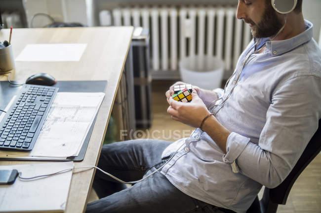 Junger Mann im Büro am Schreibtisch mit Rubik 's Cube — Stockfoto