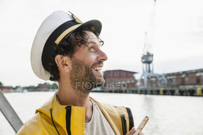 Lächelnder Mann mit Regenmantel und Kapitänsmütze am Ufer — Stockfoto