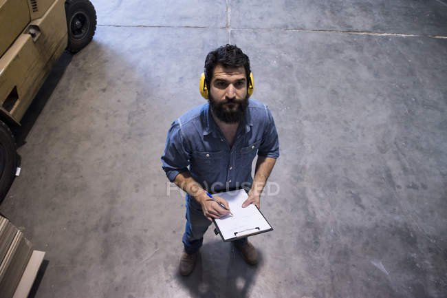 Man with hearing protection making notes in a folder in a warehouse of a factory — Stock Photo