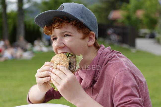 Adolescente con gorra de béisbol comiendo hamburguesa - foto de stock