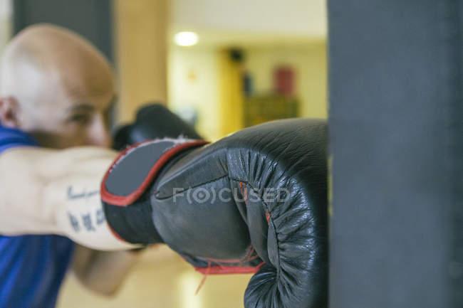 Männlichen kaukasischen Boxer schlagen einen Boxsack — Stockfoto