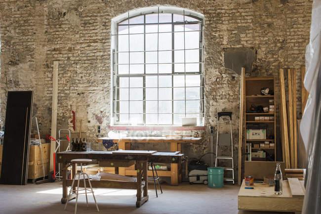 Interior de uma oficina de carpinteiro com parede de tijolo e janela — Fotografia de Stock