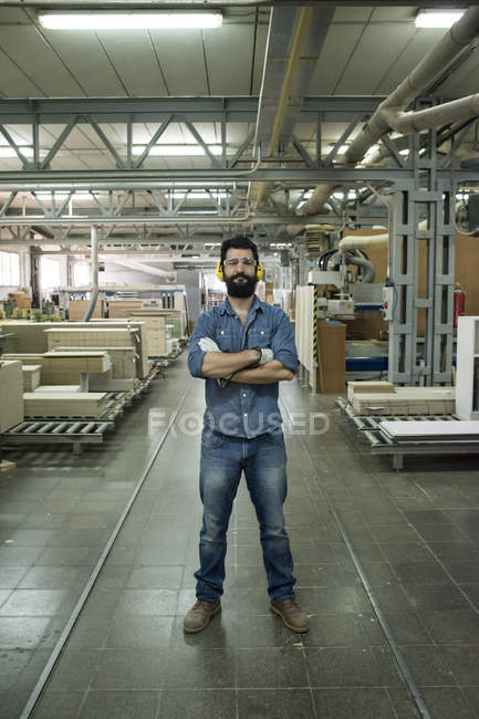 Man with hearing protection, safety glasses and gloves smiling with his arms crossed in a factory — Stock Photo