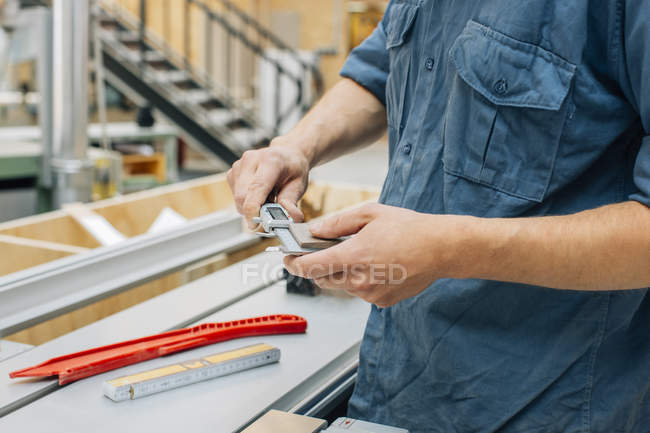 Carpenter measuring piece of wood — Stock Photo