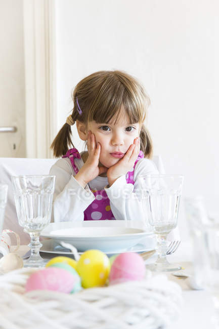 Portrait of little girl with head in hands sitting at laid table — Stock Photo