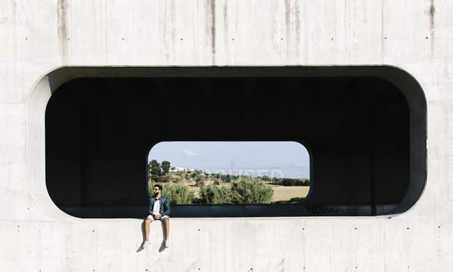 Молодой человек сидит в нише бетонной стены — стоковое фото
