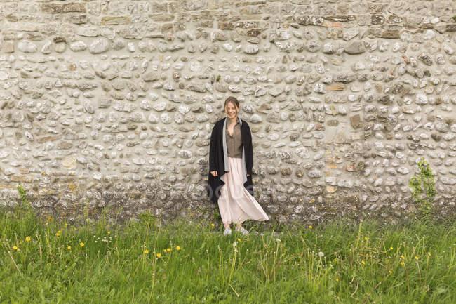 Молода жінка стоїть перед природні кам'яною стіною — стокове фото