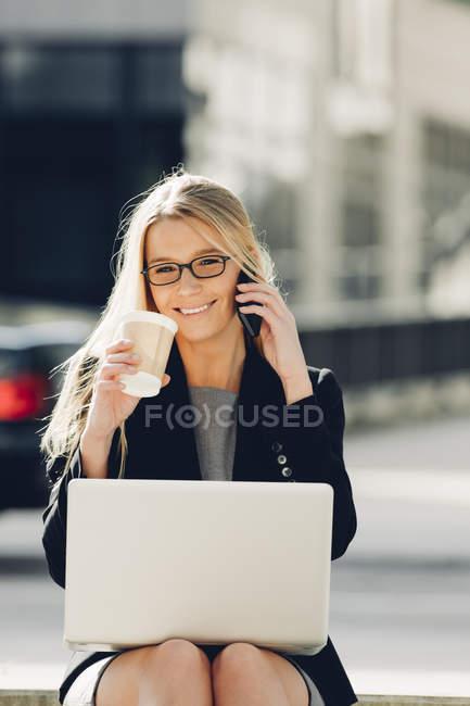 Mujer de negocios con café para ir con el ordenador portátil y teléfono celular - foto de stock