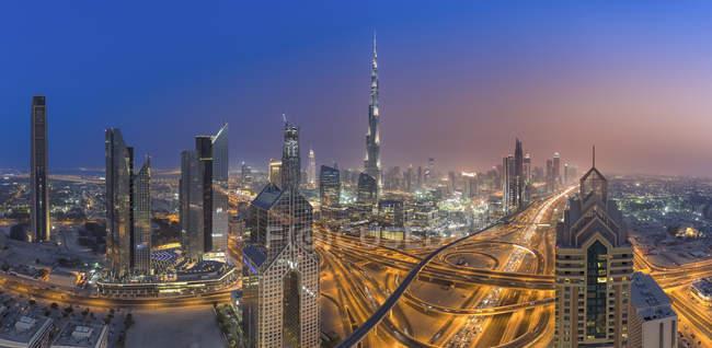 Объединенные Арабские Эмираты, Дубай, развязка на Шейх Заед Роуд и Дубая на фоне линии горизонта в сумерках — стоковое фото
