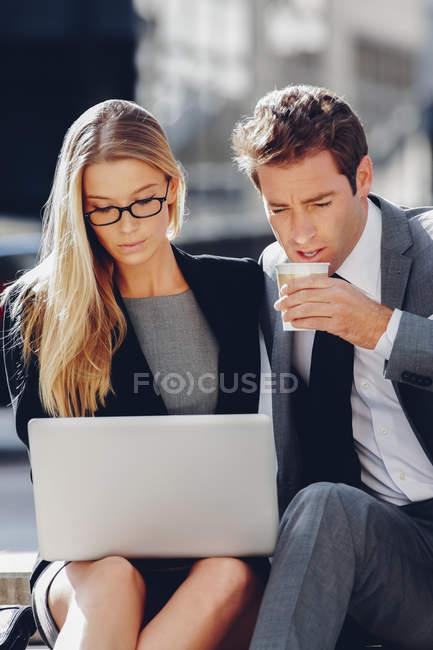 Empresário e empresária sentados do lado de fora trabalhando no computador portátil — Fotografia de Stock