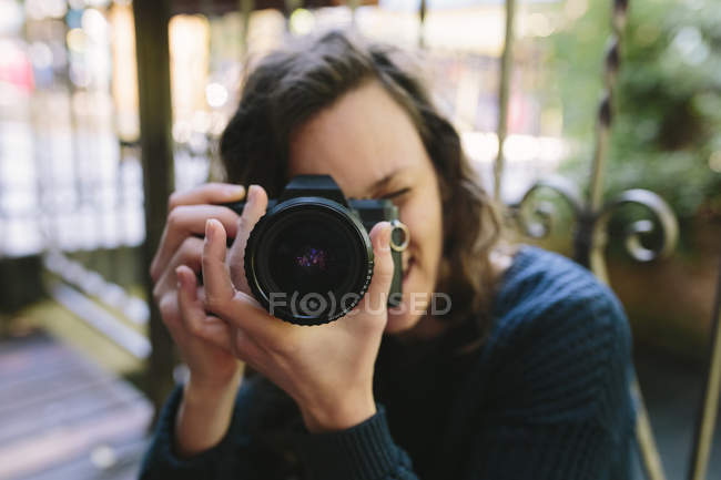 Young woman on balcony using vintage camera — Stock Photo