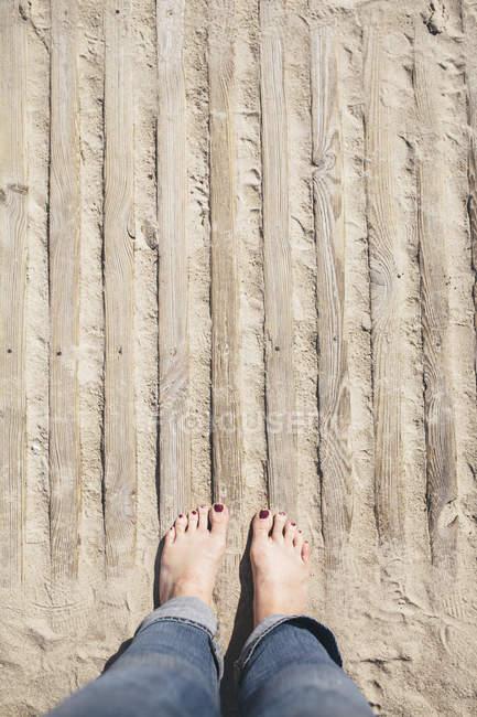 Frau steht am Strand, Teilsicht — Stockfoto