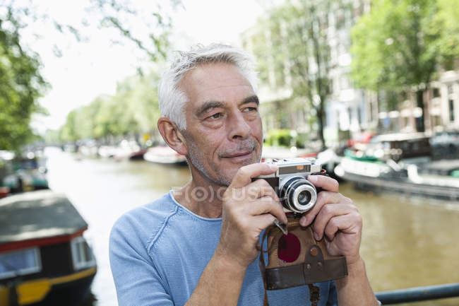 Netherlands, Amsterdam, senior man taking a picture with analog camera at town canal — Stock Photo