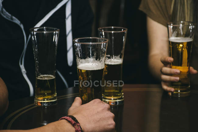 Cropped image, group of people with glasses of beer on table in bar — Stock Photo