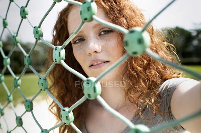 Portrait d'adolescente rousse regardant à travers le net — Photo de stock