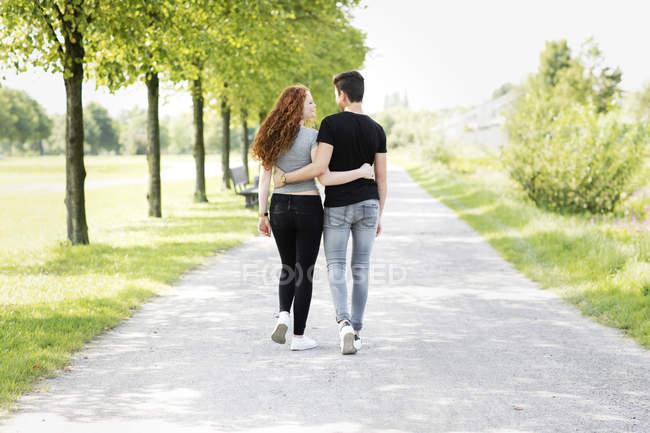 Couple adolescent amoureux marchant bras dans le bras — Photo de stock