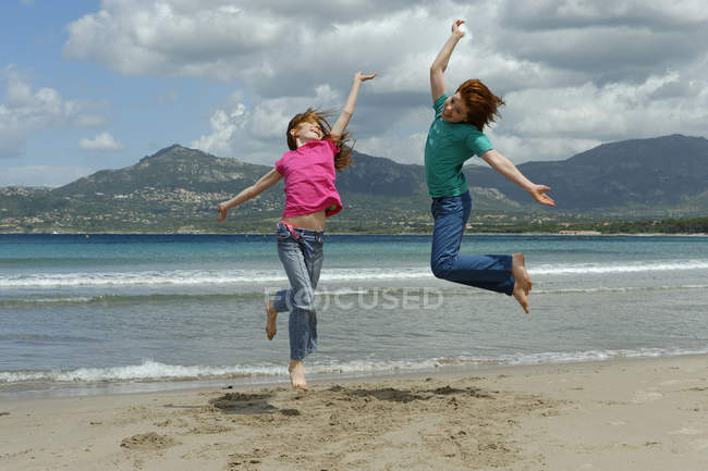 France, Corsica , Calvi, two children jumping in air on beach — Stock Photo