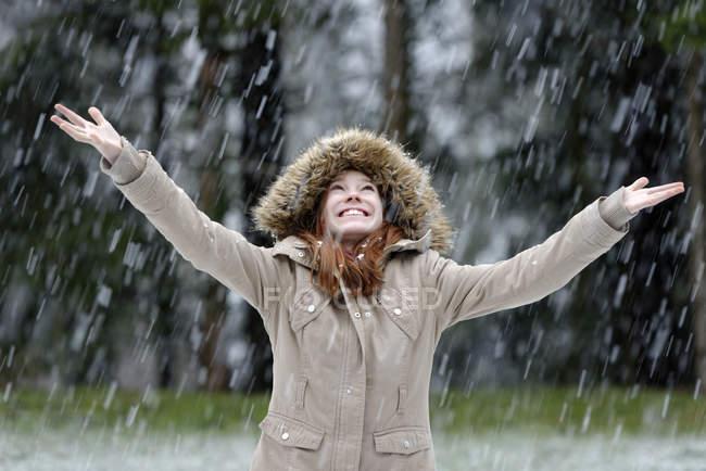 Девушка, наслаждаясь снега осенью, начало зимы — стоковое фото