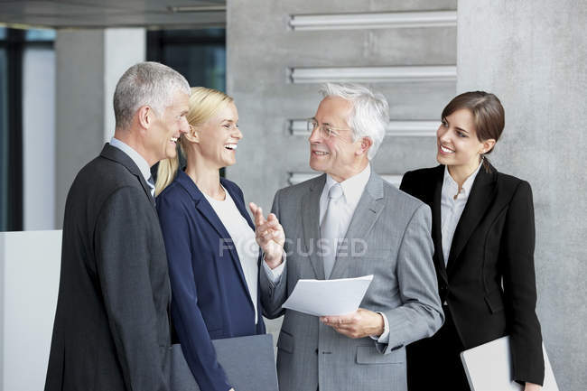 Happy business colleagues discussing document office lobby — Stock Photo