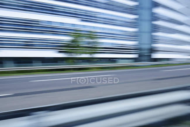 Edificio sfocato per uffici con autostrada urbana in primo piano, Germania — Foto stock