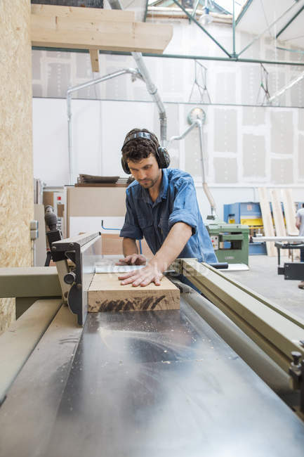 Carpenter working with sawing machine — Stock Photo