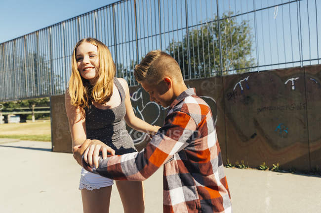 Teenage boy teaching girlfriend skateboarding — Stock Photo